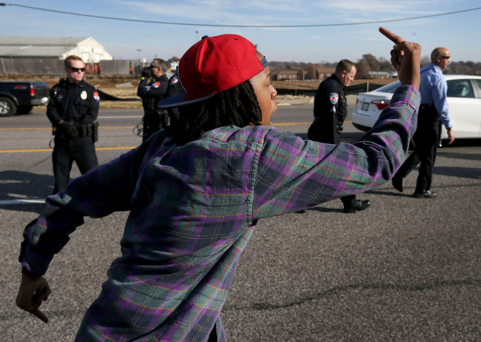 A protester balances along the curb while marching past a line of police flipping them off during a demonstration along Hanley Road on Saturday, Nov. 29, 2014.Photo By David Carson, dcarson@post-dispatch.com