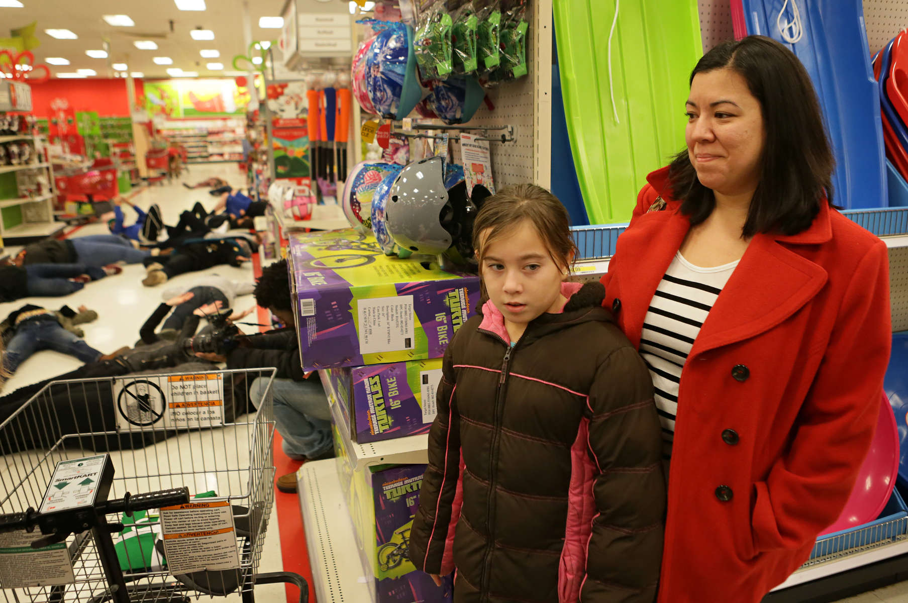 Amelia Alonzo, 9, and her mother Tracy Alonzo look over an aisle where protesters were holding a 4.5 minute die in at the Target in St. Louis County off of South Lindbergh Boulevard on Sunday, Nov. 30, 2014.  {quote}We're explaining to her that people need their voices to be heard and that there is nothing scary going on here{quote} said Tracy Alonzo {quote}We support the protesters, I was was excited to see them here{quote}.  The protesters marched around the store and chanted for 20 minutes before leaving.  Other shoppers had a different reaction to the protests and were visibly shaken by what they saw and heard. Earlier the protesters also marched and chanted in the Walmart off of Telegraph Road. Both stores announced they were closing early and police ordered the protesters to leave, which they did. Photo By David Carson, dcarson@post-dispatch.com