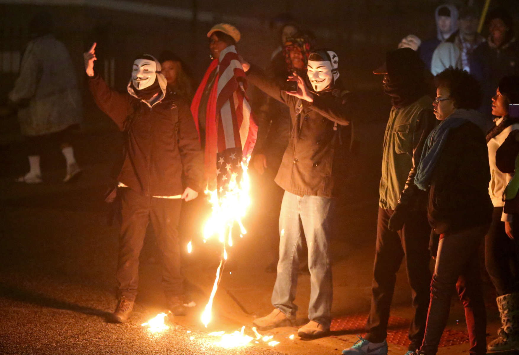 Protesters burn an American flag across the street from the Ferguson police department to taunt National Guard troops and police lined up outside the station on Thursday, Dec. 4. 2014.  After the flag burned protesters threw the flag on the ground and National Guard troops walked across the street and picked up the charred remnants of flag so they could properly dispose of it.Photo By David Carson, dcarson@post-dispatch.com