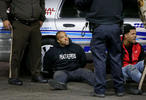 Two men arrested by police during a fight are seated next to a police cruiser on Wednesday, Dec. 24, 2014 on the lot of a gas station where teenager was fatally shot late Tuesday Dec. 23, 2014 at a Mobil gas station on North Hanley Road in Berkeley. The fight broke out after the body of the teen was removed and police and protesters got into a shoving match.Photo By David Carson, dcarson@post-dispatch.com