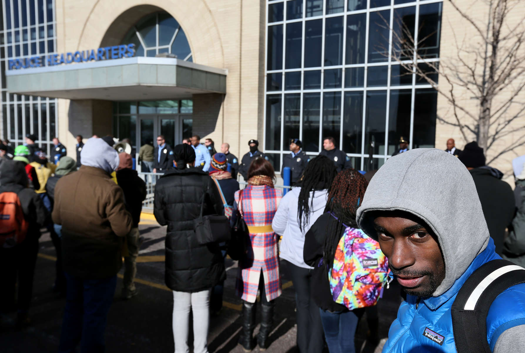 Protest leader Deray McKesson(right) stands in the crowd of protesters as police officers line up protecting the entrance to the St. Louis Police Headquarters after the police pushed out the crowd trying to rush in and occupy the lobby of the station on Wednesday, Dec. 31, 2014.  Photo By David Carson, dcarson@post-dispatch.com