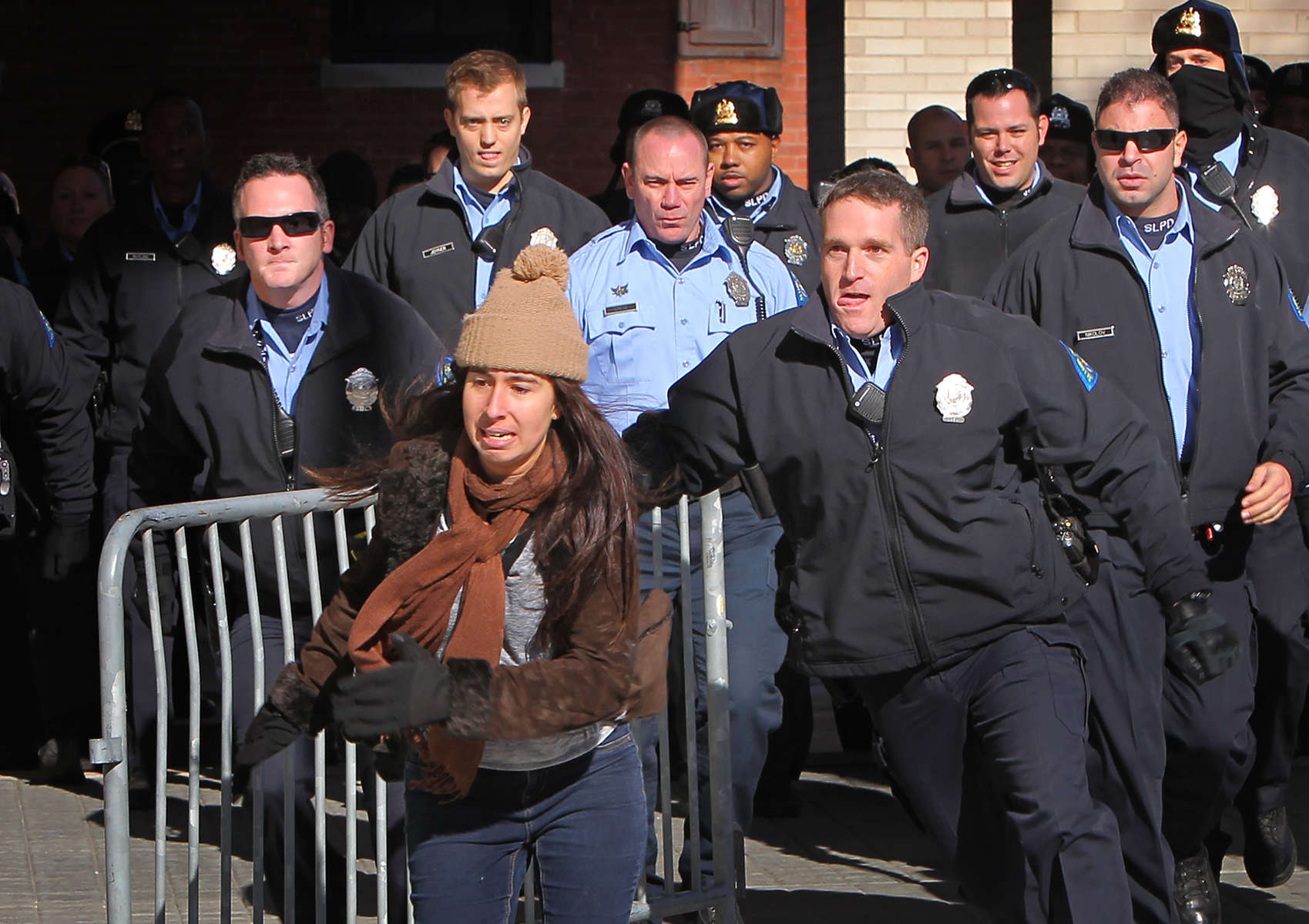 A protester runs away from police after she pushed a metal barricade in their direction outside the St. Louis Police Headquarters on Wednesday, Dec. 31, 2014.  She was arrested a short time later.Photo By David Carson, dcarson@post-dispatch.com
