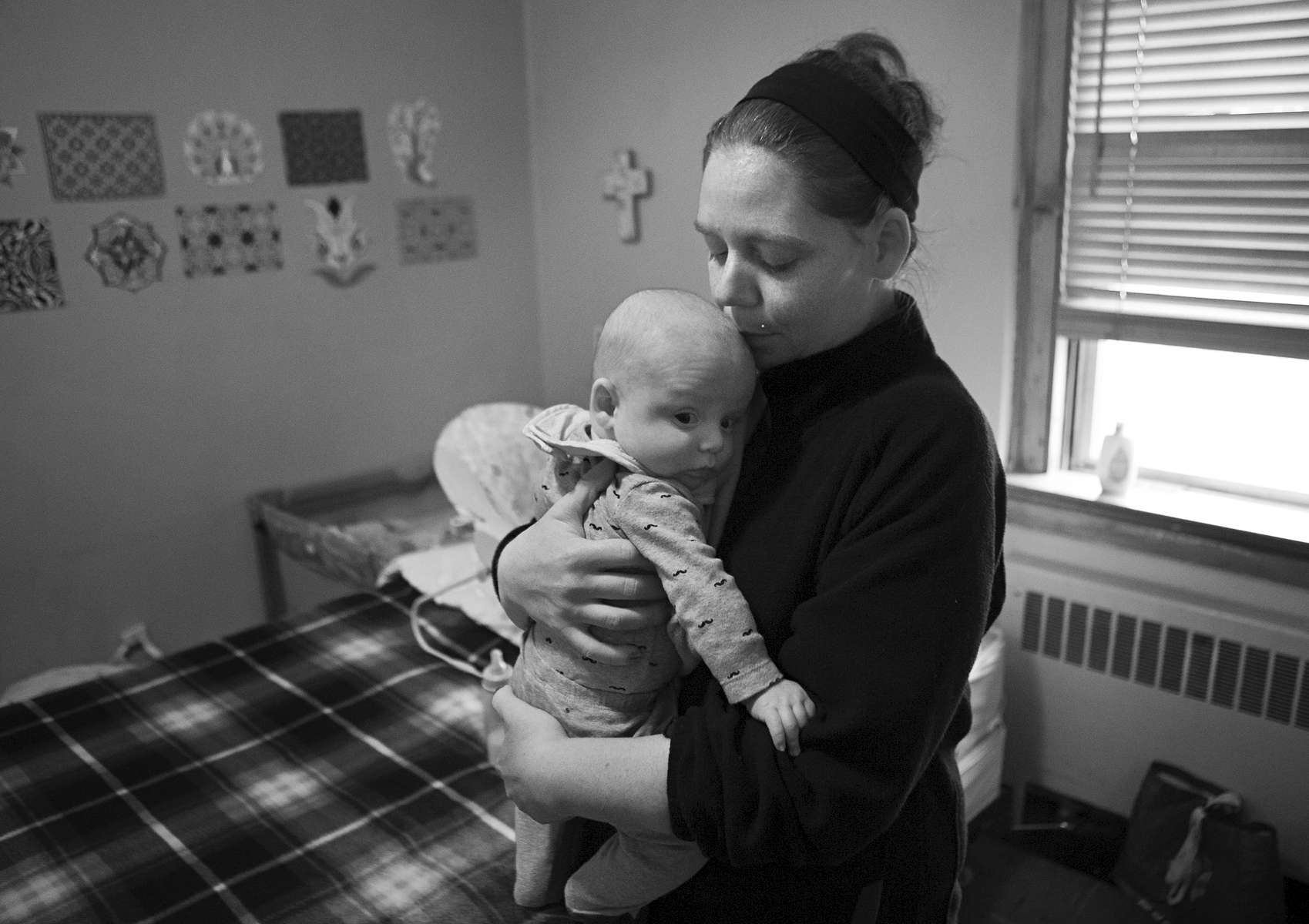Camden, 4 months, is snuggled by his mother Amanda Davis in their private room at a Queen of Peace Center maternity home in the College Hill neighborhood of St. Louis on Thursday, Feb. 23, 2017. Davis, a recovering heroin addict, entered the Queen of Peace program to help her kick her heroin addiction when she found out she was pregnant with Camden. She is taking weekly drug tests now to prove that she is clean and will soon be moving into her own apartment. Her hope is after proving she is clean and moving into her own apartment she'll be able to regain custody of her other children that were taken away by the state when she was using drugs.
