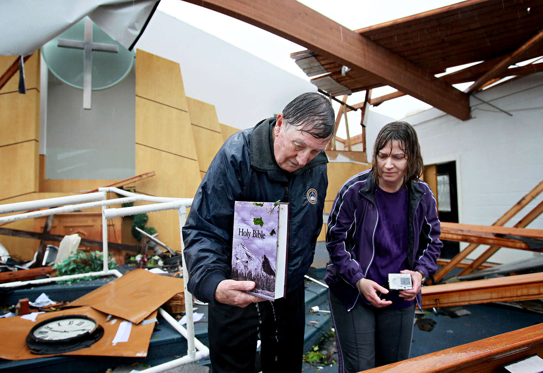 Saturday April 23, 2011--Larry Doggett, left, and his daughter Joni Bellinger salvage a bible from the debris in the sancuary of the Ferguson Christian Church after a tornado ripped the roof off the church on Friday night.  {quote}We had plans for Easter and God had other plans{quote} said Bellinger.  Thirty-one people who were watching Passion of the Christ at the church took shelter in the basement, hiding under tables and in the bathrooms, as the tornado slammed into the church.  No one was seriously hurt in the incident.  David Carson     dcarson@post-dispatch.com