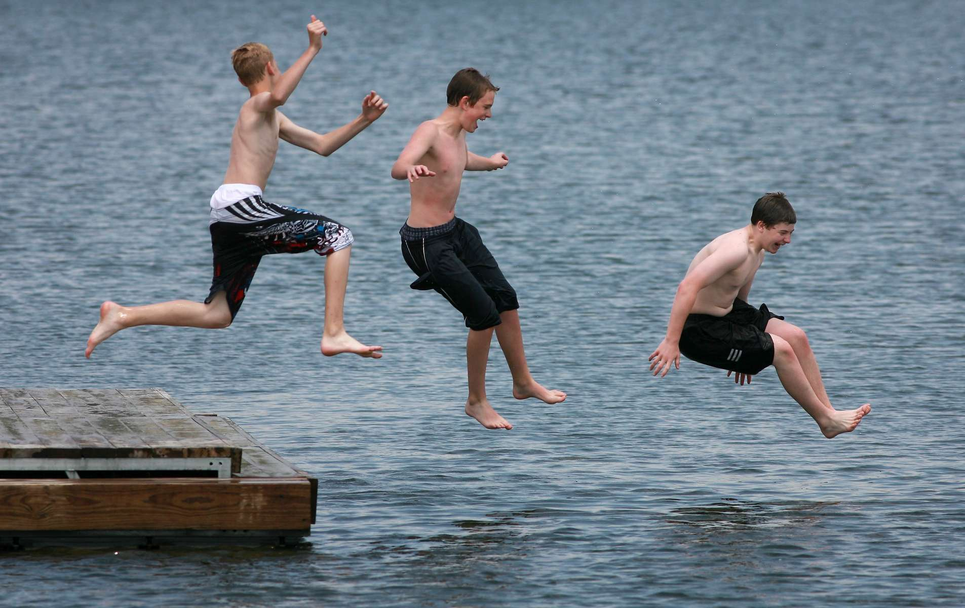 Friends Patrick Schertzer, left, Brett Ware, center, and Curtis Vitale take flying leaps into a man made lake at the New Town development in St. Charles County. Tempatures are expected to remain in the upper 80's and lower 90's for the through the weekend.