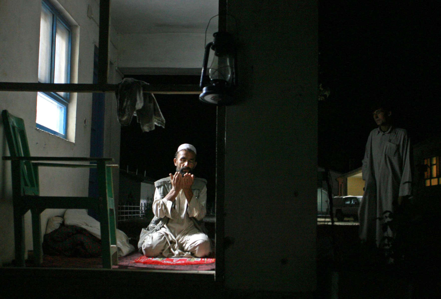 Afghanistan Five Years Later-Power--A guard performs his prayers bathed in the glow of an electric light in  Dasht-e Qal'eh, a small town in northestern Afghanistan.  While the town only receives three hours of power a night, five years ago there was none.