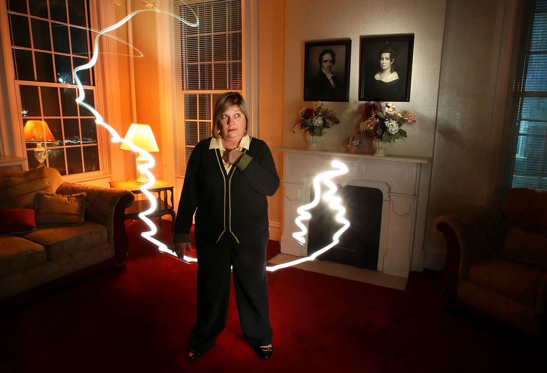 Michelle Giessman, director of student housing at Lindenwood, stands in the common area of Sibley Hall on the Lindenwood campus in St. Charles. For decades, freshman at Lindenwood University have heard the tales about deceased founder Mary Sibley roaming the campus, Giessman and a few professors and long time staffers say the stories are real. A picture of Mary Sibley can be seen to the right hanging on the wall. This image was made during a 15 second exposure using a flashlight to light the room, the technique is called painting with light.
