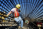 Friday July 25, 2003--Local 396 Iron Worker Crystal Farris, of Bourbon, Mo., climbs out of a rebar cage that will be sunk into the ground and filled with concrete to create the foundation for a bridge in the MetroLink expansion project on Forest Park Parkway.Photo By David Carson/PD