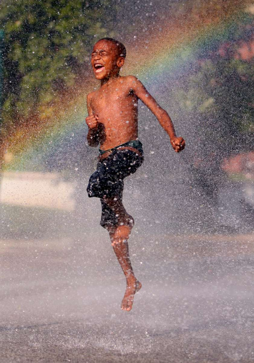 Antonie Baker, 8, leaps through the spray of a cooling station that was set up in front of the Gamble Community Center in St. Louis. An excessive heat warning was issued by the National Weather Service for the St. Louis area.
