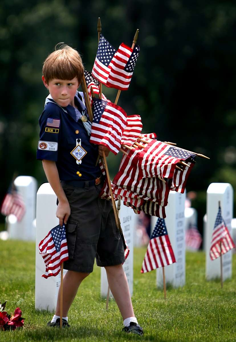 Cub Scout Nick Kollar, 8, from Eureka, places flags in front of head stones at Jefferson Barracks National Cemetery. Kollar was one of more than 5,000 local scouts who showed up to help place flags at the more than 139,000 head stones at the cemetery. This was the 61st annual Memorial Day {quote}Good Turn{quote} event that was sponsored by the Gravois Trail District of the Greater St. Louis Area Council, Boy Scouts of America.