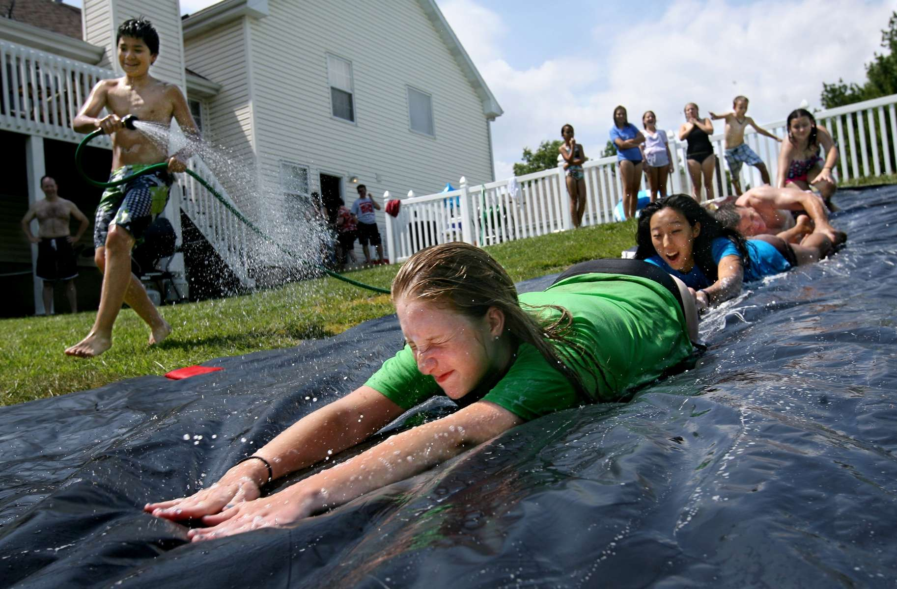 Grace Wickham (front), Rachel Hutson (center), Matt Wickham, and Reilly Newton get some help from Noah Cochran (left) as he hoses down the plastic sheeting while they launch themselves down a homemade Slip 'n Slide during a party at the Wickham's home in Weldon Spring on Monday May 28, 2012.  The Wickhams made the slide from a 100 foot roll of plastic sheeting, some sprinklers to wet the slide and dish soap to make it slippery. Photo By David Carson, dcarson@post-dispatch.com