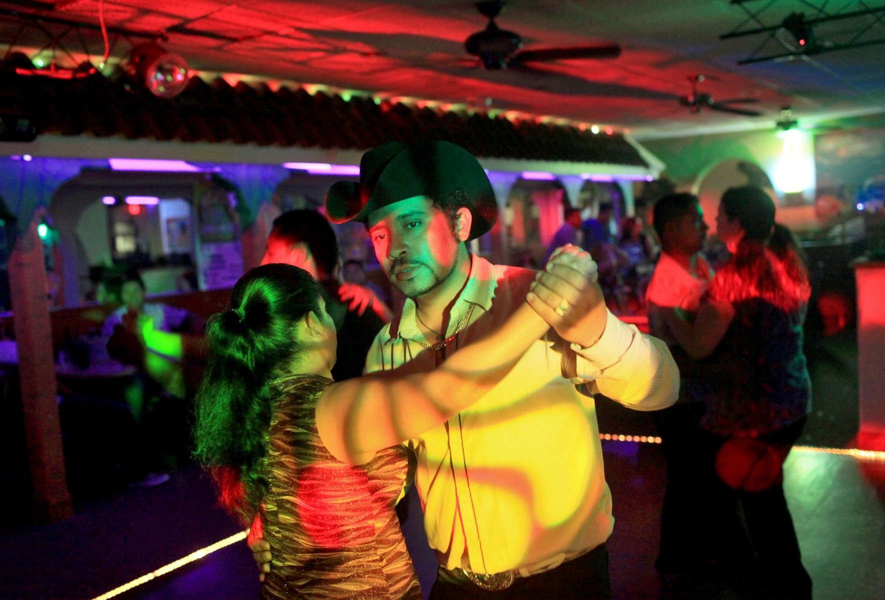 Martin McDrano (center) and Alberta Mejia dance to the music at the Acapulco Restaurant and Lounge in St. Ann. Emestina Zegar, owner of the Acapulco, thinks fewer people are frequenting her business because they fear being stopped by the St. Ann police.