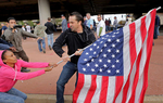 Michael Brown protesters fight to regain control of a flag that was taken by a football fan (right) leaving the Edward Jones Dome after the St. Louis Rams game in St. Louis on Sunday, Oct. 19, 2014.  Several fights erupted in a confusing and hectic scene as fans and protesters mixed after the game. Police arrested two protesters but no fans as a result of the melee.