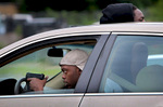 A man with a drawn gun watches police in his side rear view mirror as he drives slowly away from a line of advancing police trying to clear protesters off of Page Boulevard near the intersection of Walton Avenue on Wednesday, Aug. 19, 2015.St. Louis Post-Dispatch Photo