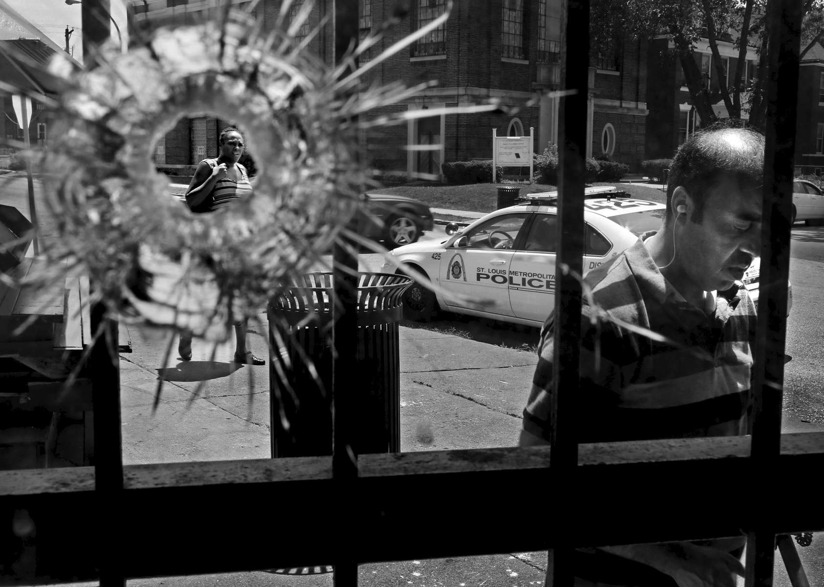 Renee Swink (left) is framed in a bullet hole punched through the front window of Yeatman Market in the 4400 block of Athlone Avenue on Monday, Aug. 3, 2015. The bullet hole is from a shooting that injured three people at about 11:30 a.m. One man suffered a gun shot wound to the leg, another man was hit in his ankle and arm and a third victim sustained a graze wound to his arm. All three victims are expected to survive. The shots were fired from a car at a man who was walking in front of the market. {quote}It's shocking{quote} said Swink whose daughter lives in an apartment above the store. Stray bullets also shattered the store's front glass doors, damaged some wood work and a soda machine. Also pictured is Mustafa Hamed (right) who was helping sweep up the broken glass.Photo By David Carson, dcarson@post-dispatch.com