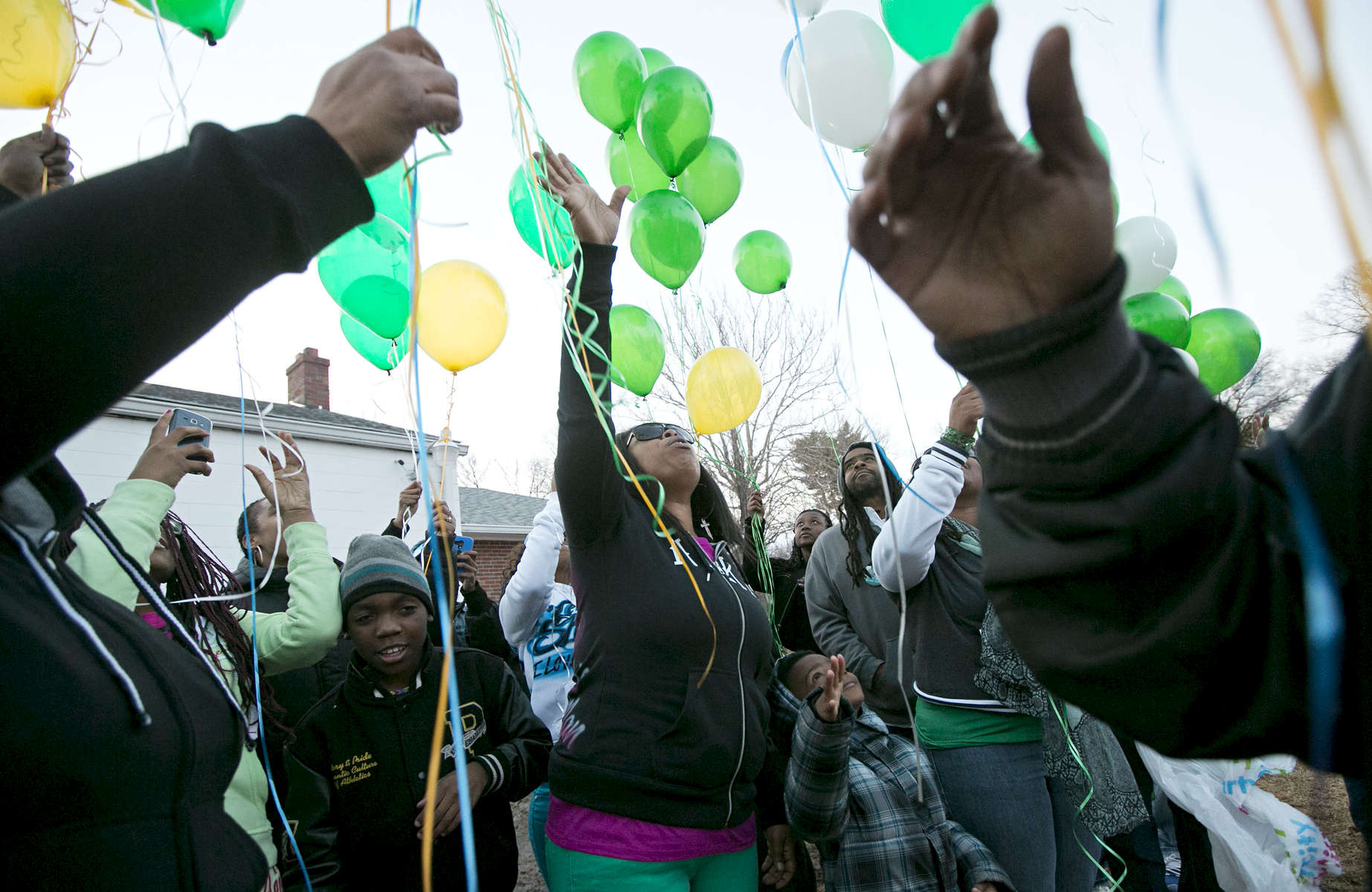 Shenelle Burgess (center) releases balloons with her family and friends at the grave of her son Pierre Childs at New Bethlehem Cemetery on Wednesday, March 5, 2014.  Police believe that Childs,16, was the unintended victim of a shooting on May, 7, 2013.  The family of Childs has been helped through the grieving and police investigation process by a minister assigned to the family by the police department.  The family gathered to release balloons to mark what would have been Childs' 17th birthday.  To date no one has been charged with Childs' murder.Photo By David Carson, dcarson@post-dispatch.com