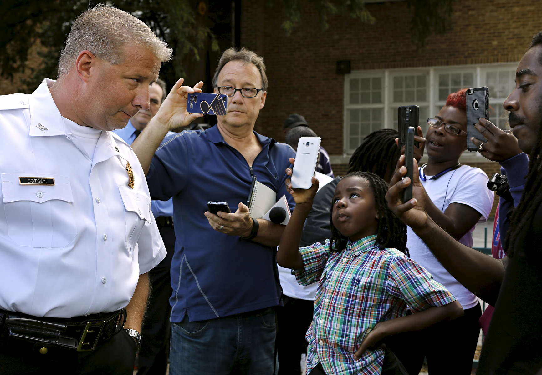 J'volte Jones, 8, holds up a cellphone to record video of St. Louis police chief Sam Dotson (left) as Dotson takes questions from the community after briefing the press about an incident where two St. Louis police officers shoot a 14 year-old boy in the 5000 block of Beacon Avenue in St. Louis on Sunday, Oct. 2, 2016. {quote}This shouldn't be their normal{quote} said J'vonte's mother Crystal Brown (not pictured). Dotson says the 14 year-old fired one shot at police who were chasing him, the police returned fire an unknown number of times hitting the boy.Photo by David Carson, dcarson@post-dispatch.com