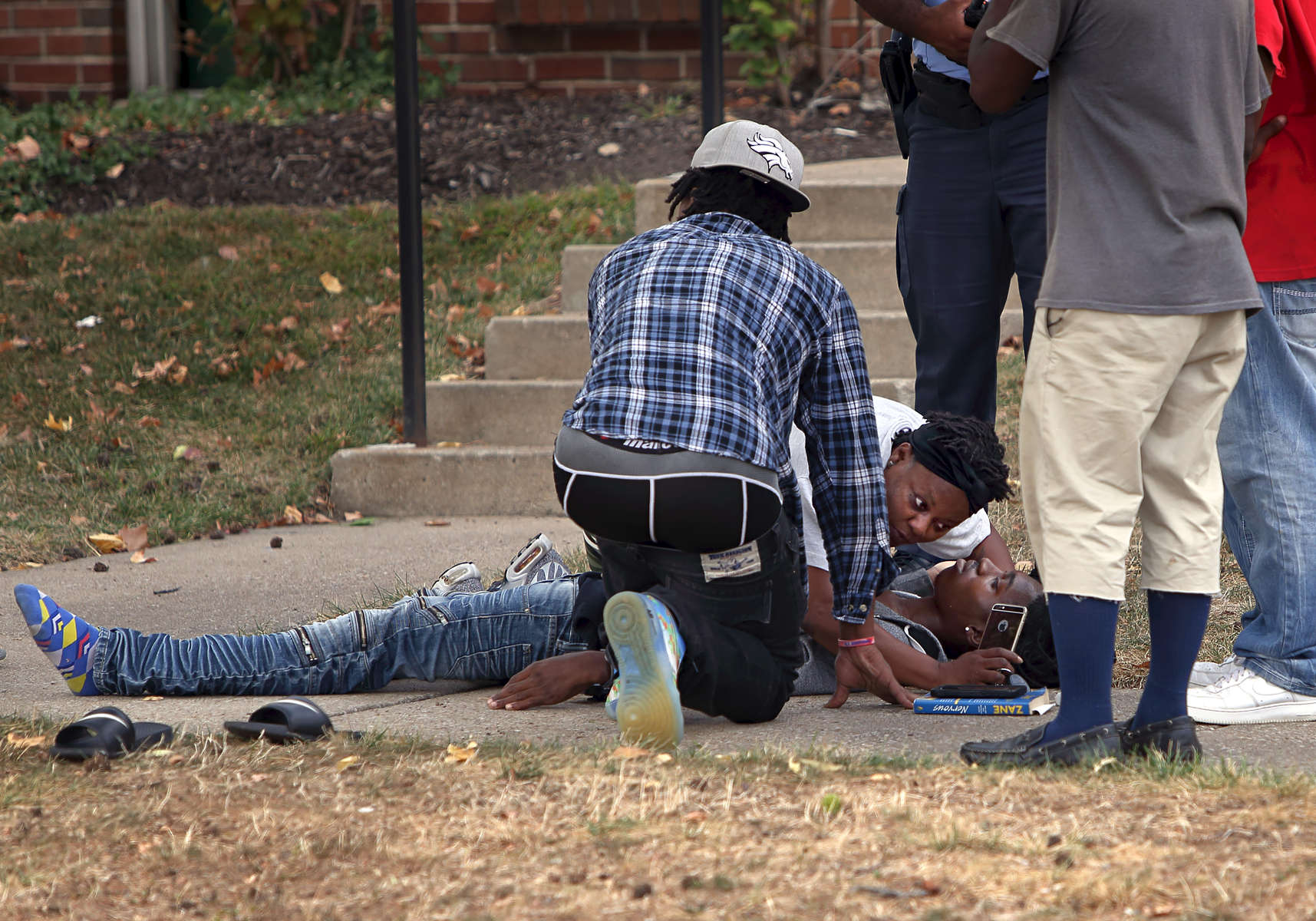 A woman leans in to talk with her nephew who was shot in the 1800 block of O'Fallon Street in St. Louis on Friday, Oct. 6, 2017. Two 20-year-old men on foot were shot by a suspect driving a silver Nissan Altima at about 2:40 p.m. Both men were transported to the hospital. One was shot twice in the upper torso and is in critical condition and the other was shot in the leg and is in stable condition.  Photo by David Carson, dcarson@post-dispatch.com