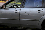 At least 14 bullet hole are visible on the driver's side of the car in a gas station parking lot at Natural Bridge Avenue and Union Boulevard where a man who was shot in the back drove to on Sunday, Nov. 5, 2017.  Police say the shooting occurred near Palm Street and Geraldine Avenue around 3 p.m. The man was conscious and breathing when he was taken to the hospital by ambulance. Another passenger in the car was unhurt by the gunfire. Photo by David Carson, dcarson@post-dispatch.com