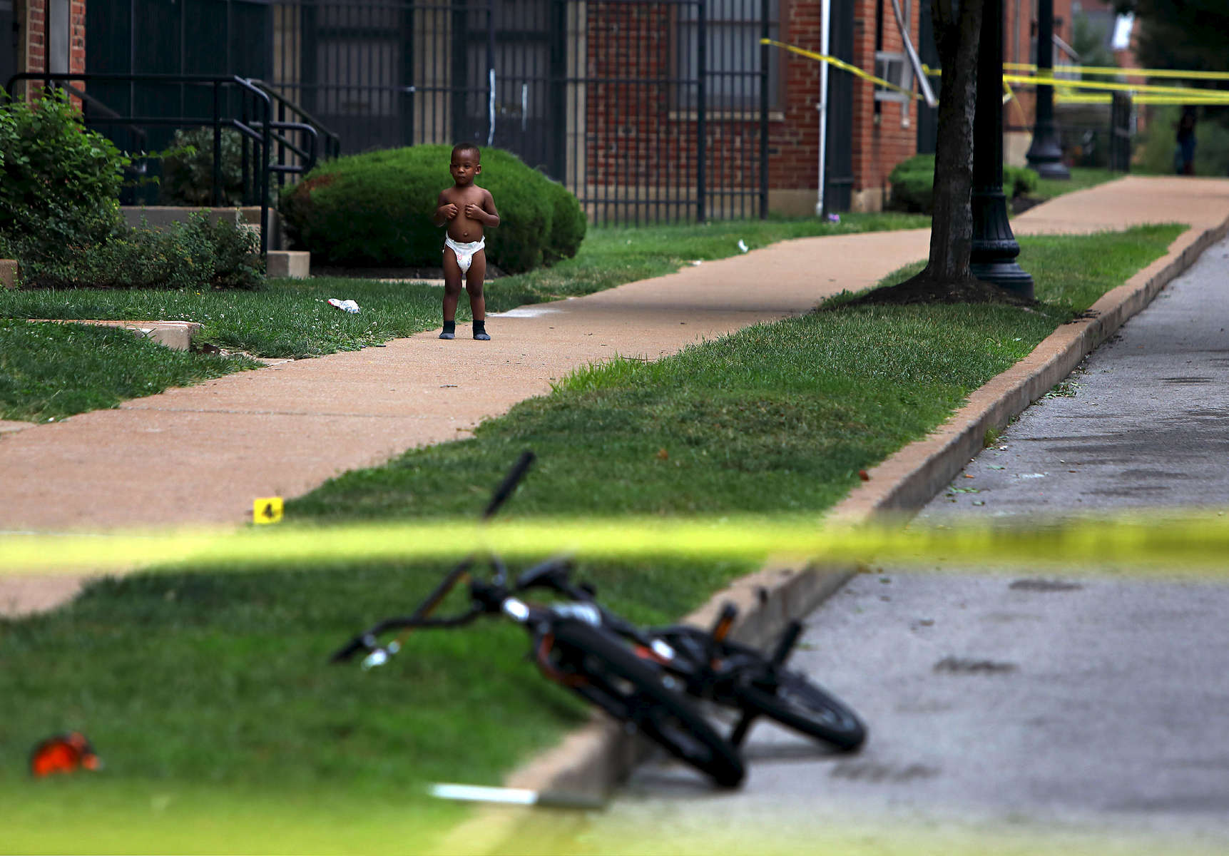 Toddler Donovan Allen, 2, stands outside his home in the 1100 block of Dillion Street as police investigate a fatal shooting in the 1400 block of Kealty Lane in St. Louis on Monday, Aug. 7, 2017. Donovan's mother, not pictured, was sitting on the front steps of her home to the left watching police investigate the scene. Police tape and evidence markers denoting bullet casings were put up right outside the front steps of the Allens home. It was the third fatal shooting in a month that occurred within 100 yards of Donovan's home. The suspect in the shooting returned to the scene driving a minivan and surrendered to police, who recovered a gun from the vehicle.Photo by David Carson, dcarson@post-dispatch.com