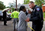Vanita Walker (left) talks with North County Police Cooperative officer Albert Haller as police investigate the scene of a triple homicide on 4500 block of Rosewood Avenue in Pine Lawn on Wednesday, April 26, 2017. {quote}That's my son's car,{quote} said Walker as she pleaded to be let into the crime scene so she could identify her son. Walker tried to calm her and explain to her why she couldn't enter the scene as it was be investigated. {quote}As a human you just feel for her,{quote} said Haller a little later after Walker moved back from the police line.Photo by David Carson, dcarson@post-dispatch.com