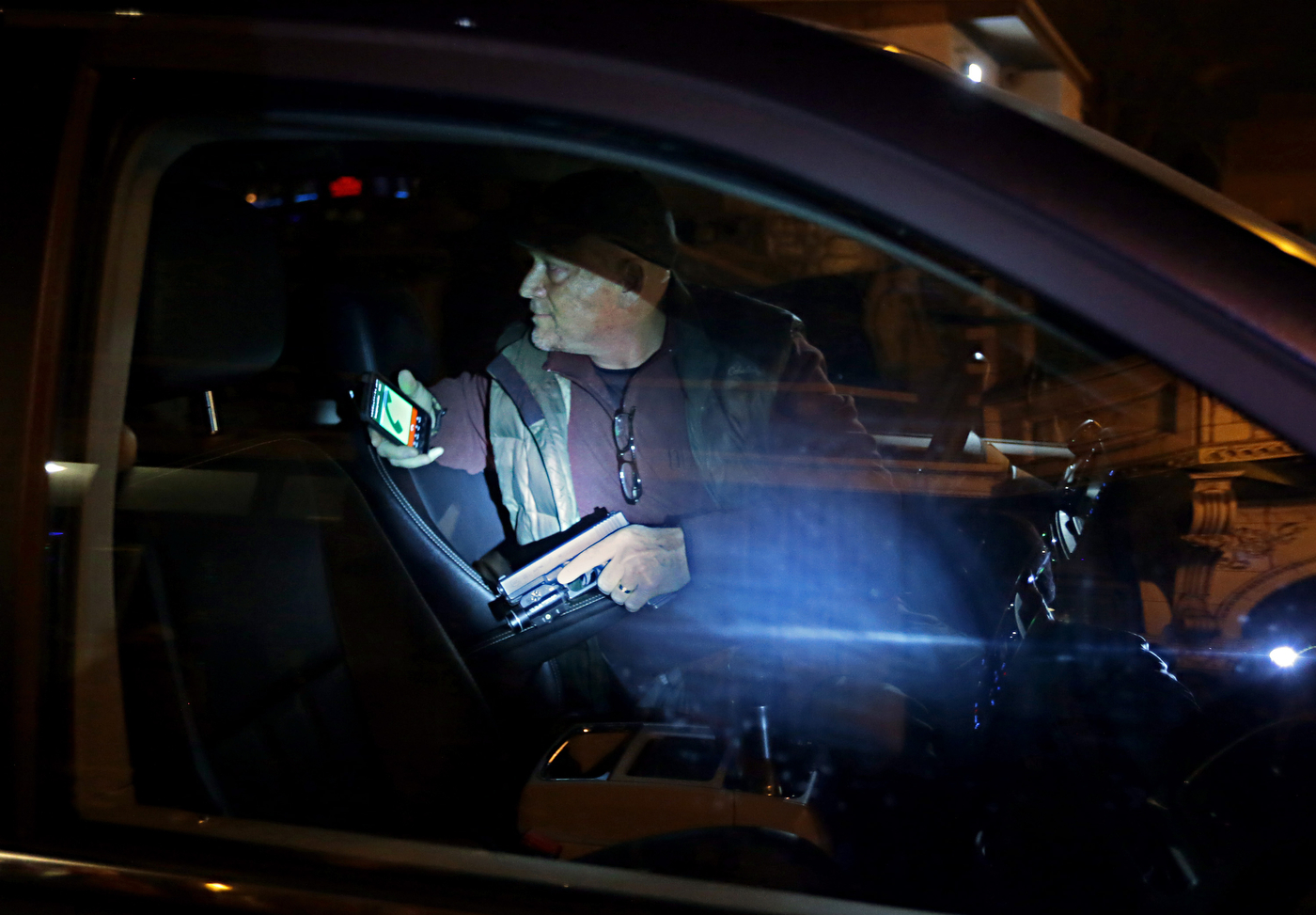 A motorist pulls his gun and keeps an eye on protesters who broke out the rear window of his minivan along Euclid Avenue in St. Louis on Wednesday, Dec. 3, 2014. Moments before the motorist had dangerously driven through a group Ferguson protesters standing in the intersection of Euclid and Maryland Avenue. The protesters chased him down the street and surrounded his vehicle when he became stuck in traffic.
