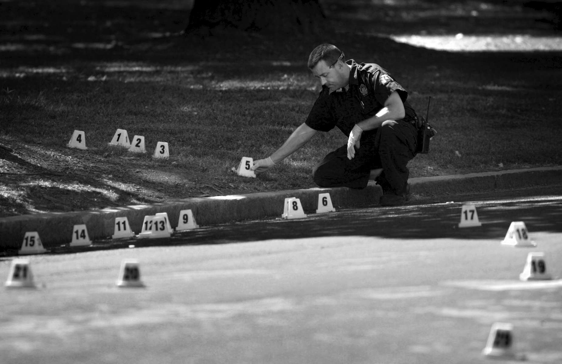 Thursday September 17, 2009--St. Louis Police Department crime scene technician Tom Burgoon places evidence markers next to all the shell casings that littered the ground near the scene of shooting at Fountain Ave. and N. Eucid Ave on Thursday.  The victim was transported to the hospital where he was listed in critical condition.David Carson     dcarson@post-dispatch.com