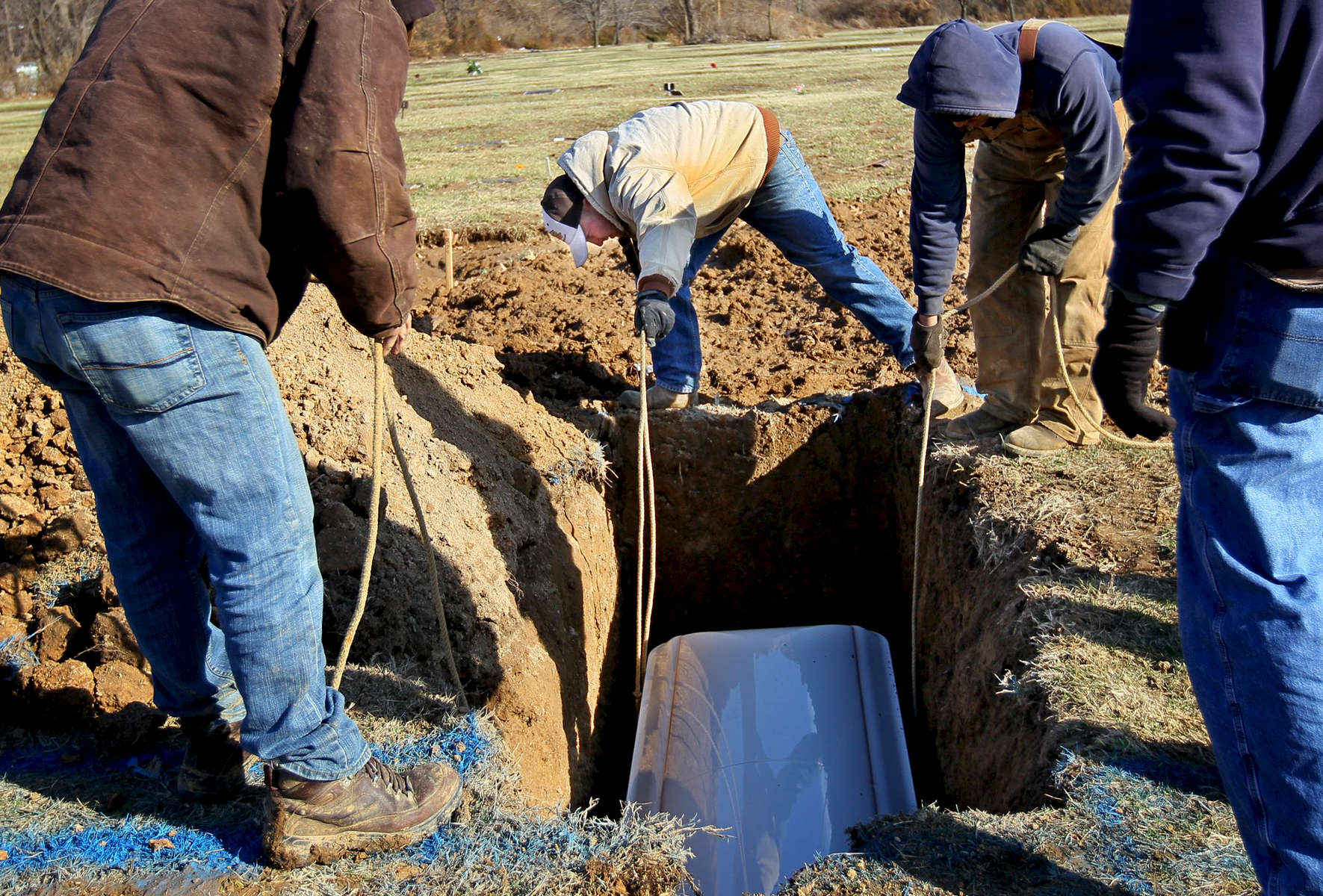 Tuesday March 1, 2011--Grave digger Adam Osborne, 24, center, and other workers from Lake Charles Park Cemetery lower 16 year-old Jade Hamilton's coffin into her grave after her funeral.  Hamilton had been sitting in a car at Mount Pleasant Park when three young men approached the car and began shooting, striking her in the neck, police said.  David Carson     dcarson@post-dispatch.com