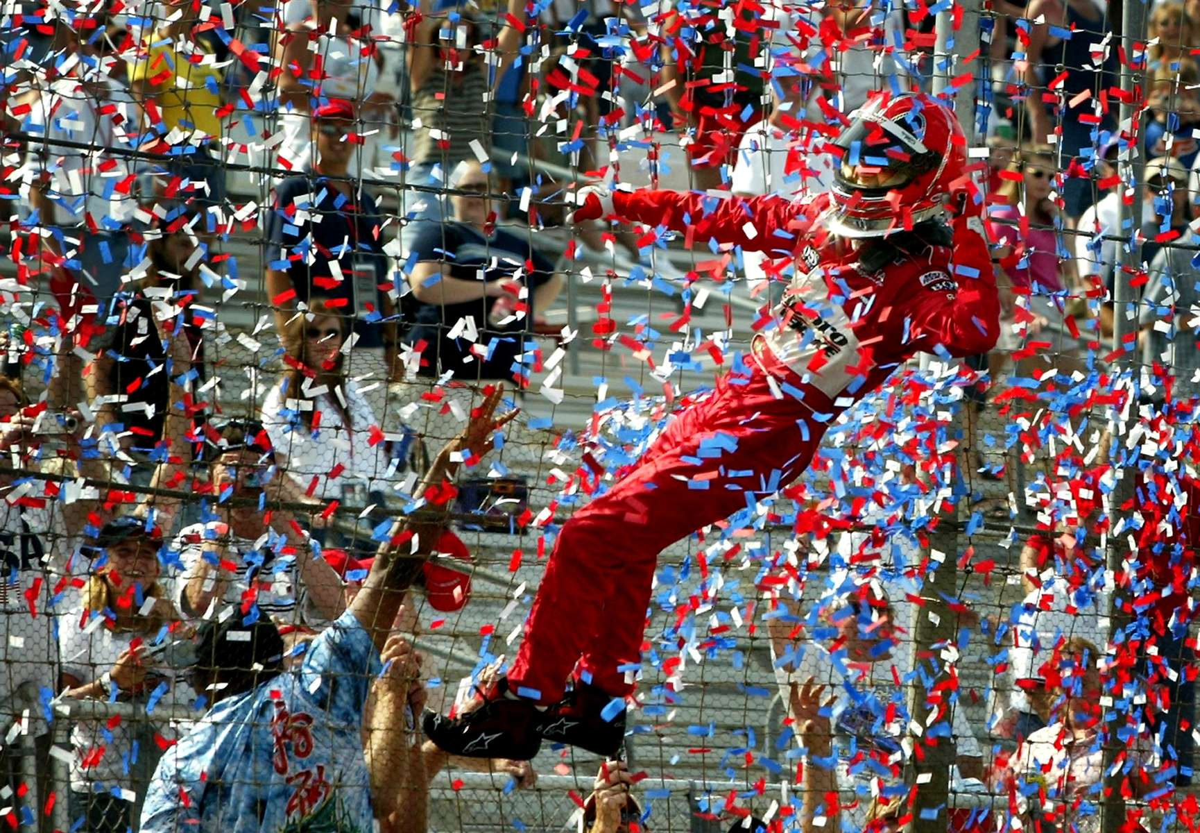 Helio Castroneves celebrates his victory by climbing the fence at the finish line after winning the Emerson Indy 250 at Gateway International Raceway.
