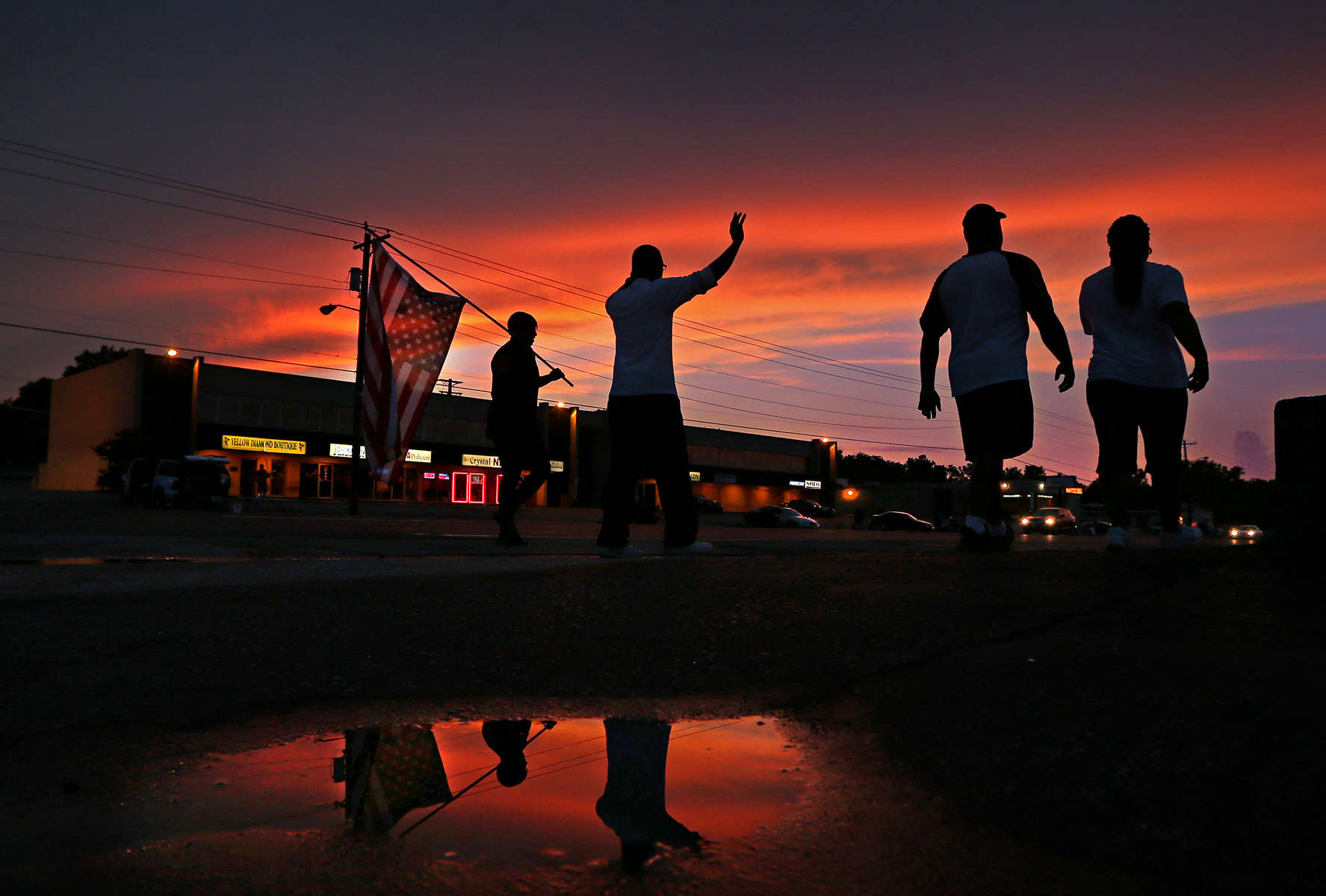 A small group protesters march along W. Florissant Avenue in Ferguson, Mo. on Tuesday, Aug. 26, 2014.  The large crowds and vocal protesters from earlier in the protests have mostly disappeared now.  Typically there has been less than a 100 people along W. Florissant protesting during the evening hours.  Some nights there have only been a couple of dozen people.