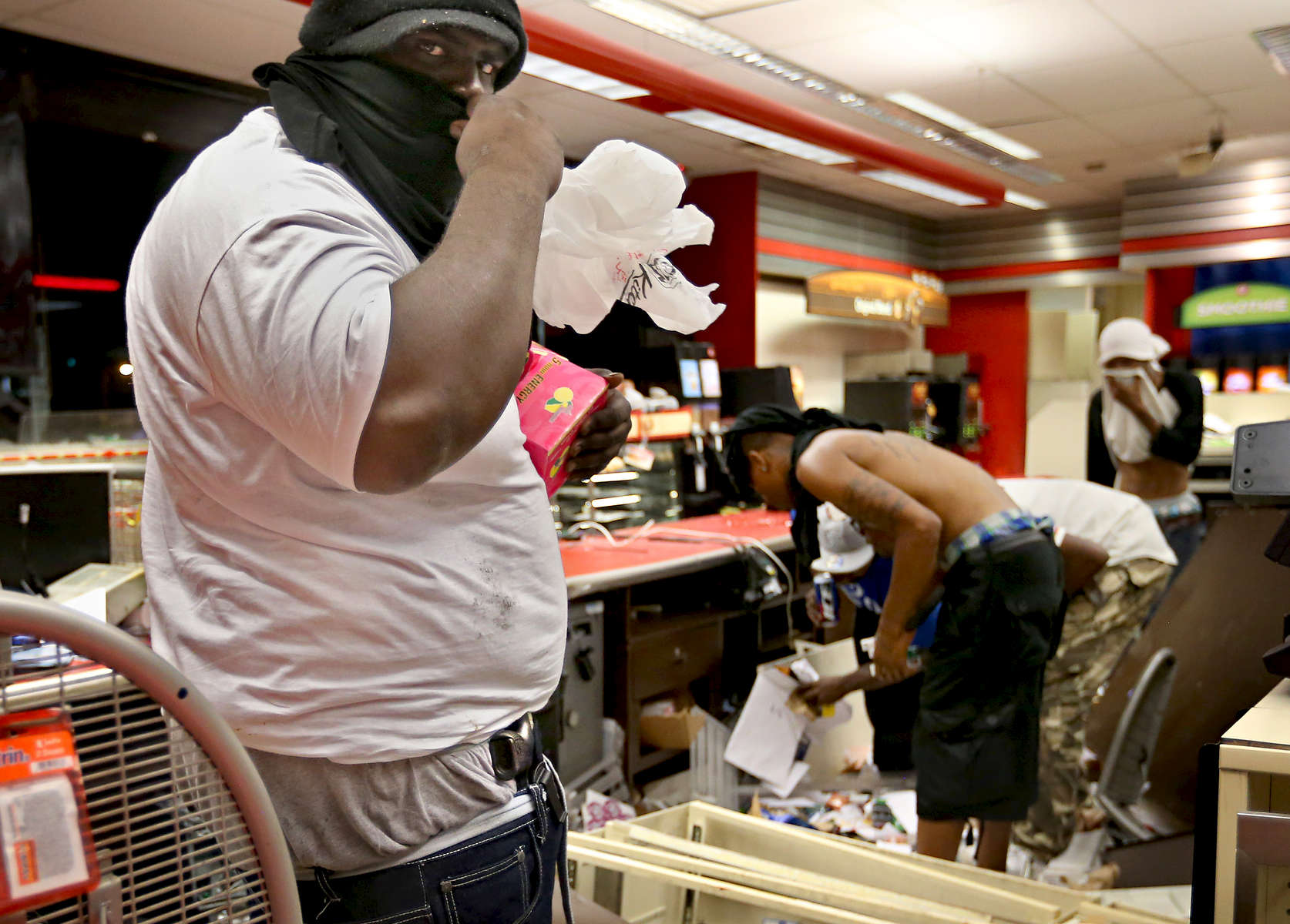 A looter armed with a gun in his waist band steals items from inside the QuikTrip on W. Florissant Avenue in Ferguson, Mo. on Sunday, Aug. 10, 2014.  Looting and riots broke out at the end of a candle light vigil for Michael Brown, an unarmed 18 year-old who was shot and killed by police.  The looters later burned the store after police withdrew from the area to wait for reinforcements.