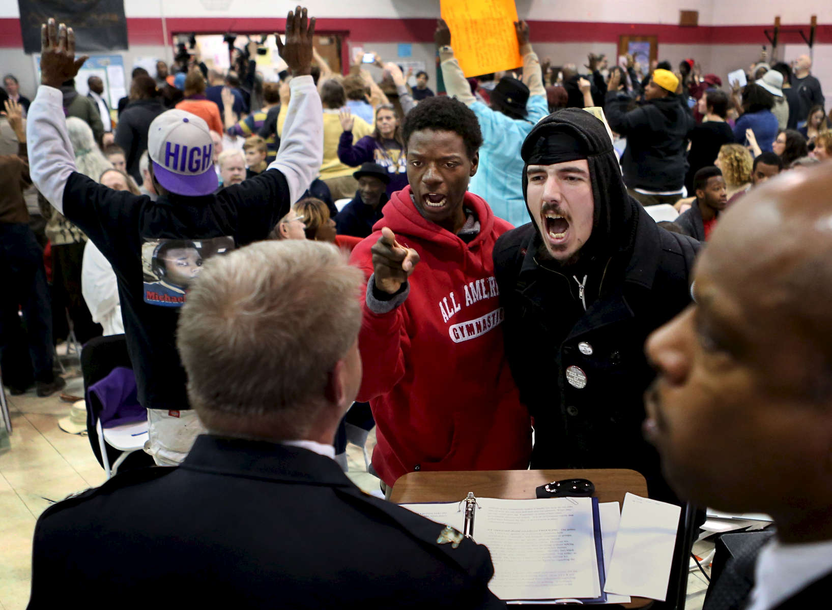 Joshua Williams (left center) and Nicholas Austin Jackson shout at St. Louis police chief Sam Dotson (left) as he tries to give a presentation during the second meeting of the Ferguson Commission in St. Louis on Monday, Dec. 8, 2014.  Some in the crowd stood and turned their back on Dotson as he spoke, others heckled him. Ferguson Commission member and Director of the Missouri Department of of Public Safety Dan Isom is pictured to the right. Isom was the St. Louis chief of police before Dotson.  The Ferguson Commission was created by the governor of Missouri to attempt to come up with solutions for the issues a raised by the Ferguson protests.