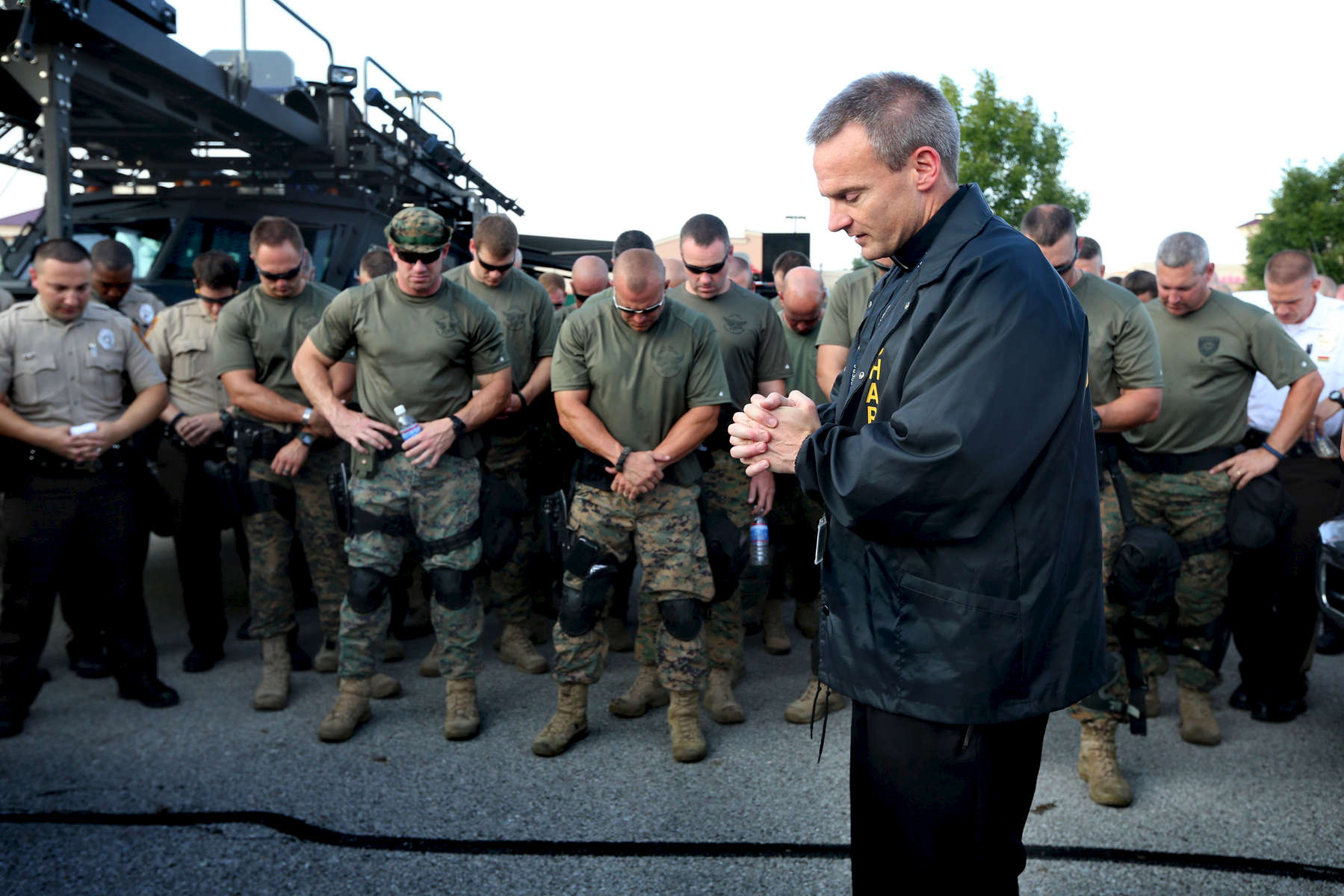 Reverend Michael Boehm says a prayer during roll call with police officers and St. Louis County Police tactical team as they make a plan for how to deal with crowds of people along W. Florissant Road in Ferguson on Monday, Aug. 18, 2014.Photo By David Carson, dcarson@post-dispatch.com