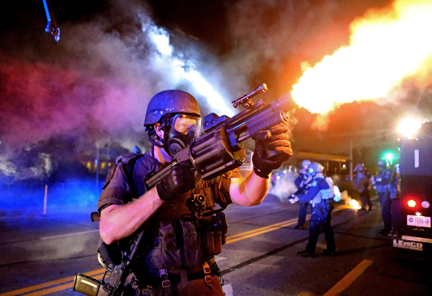 A member of the St. Louis County Police tactical team fires rounds of tear gas into a crowd of people in response to a series of gunshots fired at the police during demonstrations along W. Florissant Road near the QuikTrip in Ferguson, Mo. on Monday, Aug. 18, 2014.  Protesters also threw bottles and rocks with at least one rock striking an officer in the arm.