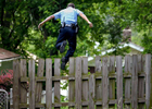 Monday June 2, 2008--Pine Lawn police officer Matthew Meinen leaps off a fence in pursuit of a suspect who fled from police that were patroling a Pine Lawn neighborhood in golf carts.  Meinen was called to scene to in his patrol car to assist when the subjects fled.David Carson | Post-Dispatch
