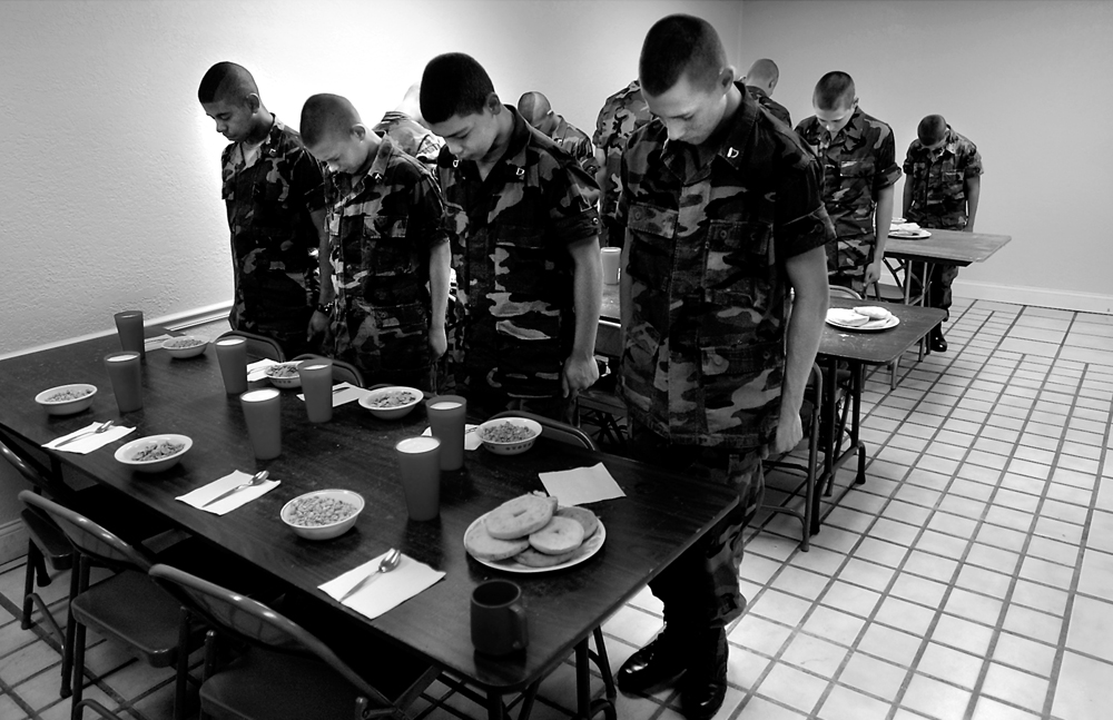 Residents stand at attention and bow their heads in prayer before sitting down to eat their breakfast in silence.