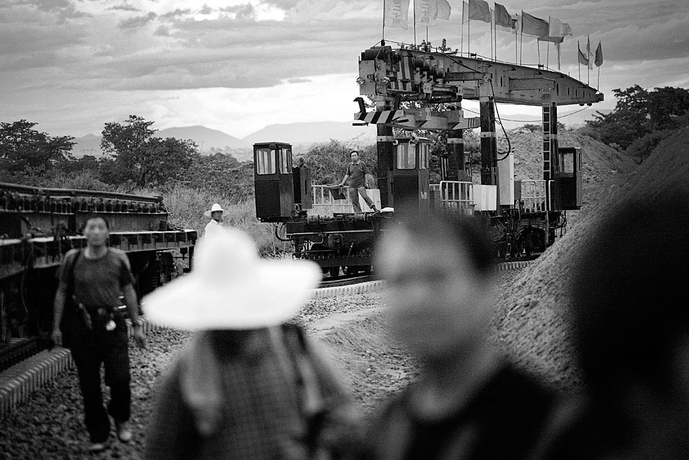 Chinese railways workers prepare to put tracks outside, Dondo, Angola, 2007.  Hundreds of workers live in rural camps along the tracks and all the equipment are imported from China. The Chinese are upgrading two railway lines in Angola.