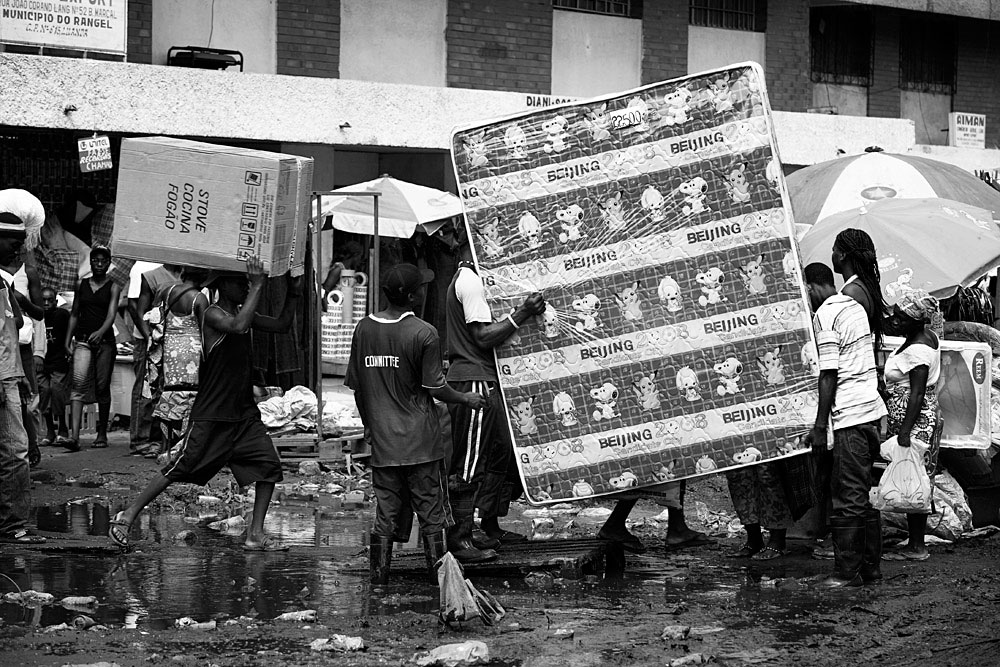 "Angolan workers carry a mattress with a ""Beijing 2008"" sign in the Chinese market, Luanda, Angola, 2007"