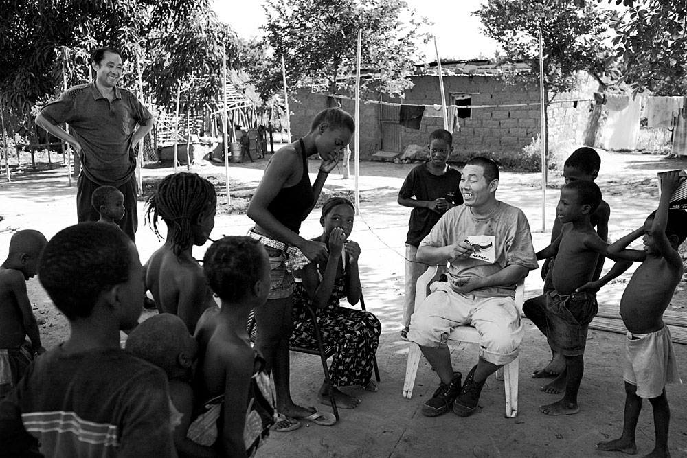 Chinese railways workers interact with Angolan villagers in a rural area, Dondo, Angola, 2007. Hundreds of workers live in rural camps along the tracks and all the equipment are imported from China. The Chinese are upgrading two railway lines in Angola.