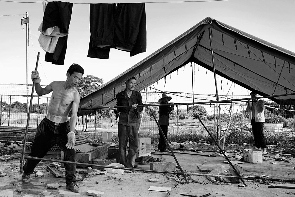 Chinese railway workers dismantle a workers tent camp, Dondo, Angola, 2007. Hundreds of workers live in rural camps along the tracks and all the equipment are imported from China. The Chinese are upgrading two railway lines in Angola.