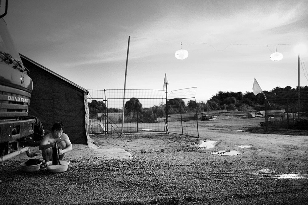 A Chinese railway worker washes his laundry in a tent camp, Dondo, Angola, 2007. Hundreds of workers live in rural camps along the tracks and all the equipment are imported from China. The Chinese are upgrading two railway lines in Angola.