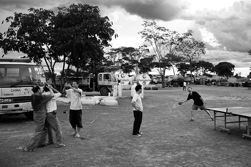 Chinese road construction workers play ping-pong in their construction yard at their rural camp, Ndola, Zambia, 2007. They are contracted to build several roads in Zambia.