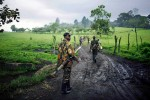 A soldier loyal to General Laurent Nkunda, a rebel leader, walks in a field with his fellow soldiers, Kilolirwe, DRC, 2006