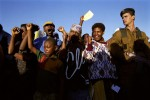 South Africans sing freedom songs while queuing to vote in the historic first democratic election on April 27, 1994 in Lindelani, Natal, South Africa. President Nelson Mandela voted here 6AM and his car passed by as these youngsters sang to honor him. Mr. Mandela served a one five-year term and retired in 1999.