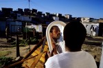 A mans face is reflected in a mirror as he cuts his beard outside his house in Khayelitsha, the biggest black township outside, Cape Town, South Africa, 2001