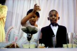 Children join a toast while attending a wedding reception in Soweto, Johannesburg, South Africa, 2005. A couple celebrated a white wedding in a rented hall. Soweto is South Africa's largest township and it was founded about one hundred years to make housing available for black people south west of downtown Johannesburg. The estimated population is between 2-3 million.