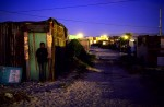 A teenage girl stands outside the family home at night in Khayelitsha, outside Cape Town, South Africa, 2003. About 1 million people live here in poor conditions, most of them coming from the rural areas to look for work in Cape Town.