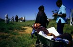 Busisiwe Mfeka, age 28, is dying of Aids and rests in a wheelbarrow, as a hospice worker drops her of with her mother at her side in Izingolweni, a rural village in Southern Natal in South Africa, 2001. South Africa has one of the highest infection rates of HIV/Aids in the world