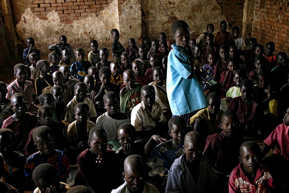 Young school children wait for their teacher during a class at St. Martine Primary School in Laliya, Uganda, 2005. Many children in Northern Uganda are afraid of being abducted by the Lord's Resistance Army (LRA). The rebel group has brought terror to Northern Uganda for almost twenty years, fighting the Ugandan government. The victims are usually children, which are abducted and used as child soldiers and sex slaves.