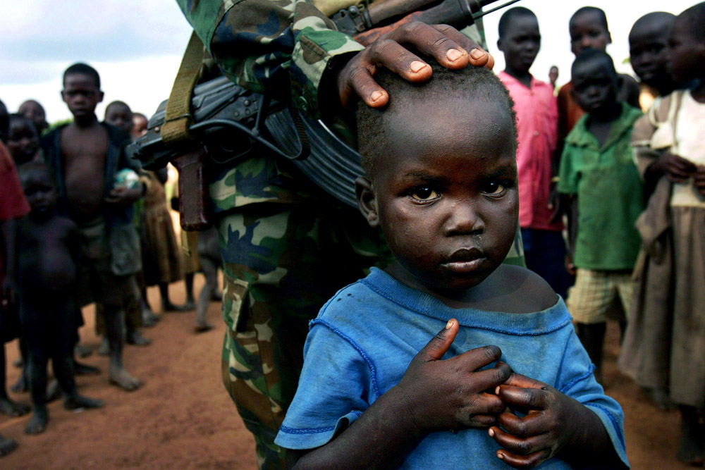 A soldier from the Ugandan National Army interact with refugee children in Pagak, camp for displayed people in northern Uganda, 2005. About 1.5 million people have fled villages and live in about 180 squalid Internally Displaced People (IDP) camps, which has changed rural life in Northern Uganda.